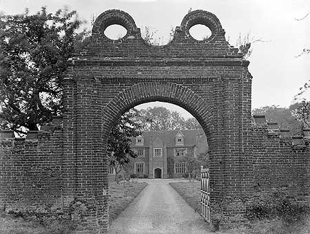 Breccles Hall, Norfolk, seen here through its entrance gateway, is an example of a brick-built 16th-century manor house. By this date building in brick was quite usual.